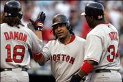 Boston's Manny Ramirez, center, celebrates his third-inning grand slam with teammates Johnny Damon, left, and David Ortiz. The Red Sox beat the Rangers, 7-4, on Tuesday in Arlington, Texas.