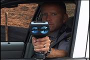 "Lawrence police officer Matt Sarna operates a radar gun at a speed trap in Lawrence. Police say drivers shouldn&squot;t count on being able to exceed the speed limit by 5 or 10 mph without getting in trouble. The law is the law, they say, not a rough ""guideline."""