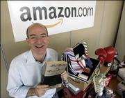 "Amazon.com founder and CEO Jeff Bezos holds a copy of ""Fluid Concepts and Creative Analogies"" by Douglas Hofstadter - the first book sold online by Amazon.com - at the company&squot;s headquarters in Seattle. The company that sells a variety of items - including those on the table next to him - was launched on the Web 10 years ago."