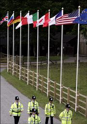Police officers walk by the flags of the G8 leaders in front of the Gleneagles Hotel near Auchterarder, Scotland. Scottish police on Tuesday promised zero tolerance for troublemakers at protests planned to coincide with the opening of the summit of leaders of the G8 group of wealthy nations, which begins today.