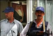 Iraqi security stands guard in front of a portrait of the king of Bahrain Tuesday outside Bahrain's embassy in Baghdad, Iraq. Bahrain's top envoy in Iraq, Hassan Malallah al-Ansari, was shot on his way to work in the Mansour district of western Baghdad. The Bahraini diplomat was treated for a shoulder wound and released, witnesses said.