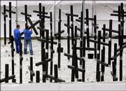 Workers tear down the crosses of the private Berlin Wall memorial near the former allied Checkpoint Charlie. Following long legal proceedings after the lease for the site expired in 2004, the memorial was dismantled Tuesday. The 1,067 crosses stood for the number of victims killed at the border from 1961 to 1989, according to the figures of the Checkpoint Charlie museum, which built the memorial.