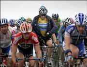 Overall leader Lance Armstrong, rear center, a six-time winner, zips his rain jacket as he pedals in the pack during the sixth stage of the Tour de France. Lorenzo Bernucci of Italy won the stage Thursday between Troyes and Nancy in eastern France.