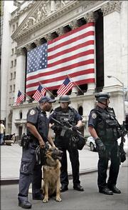 Members of New York City Police Department Emergency Services and a K-9 unit patrol Thursday outside the New York Stock Exchange. Jittery traders initially sent stock futures sharply lower Thursday after a series of explosions rocked London. Throughout the day, stocks rose as traders regained confidence in U.S. security.