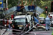 A forensic officer walks next to the wreckage of a double decker bus with its top blown off and damaged cars scattered on the road at Tavistock Square in central London. A series of explosions blamed on Islamic terrorists tore into at least three London subway trains and a double-decker bus Thursday, killing dozens and injuring hundreds.