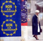 "A woman walks by posters encouraging people to vote ""no"" on the  EU constitution outside a polling station Sunday in Luxembourg. Voters approved the embattled European Union constitution, a treaty that many in the 25-nation bloc say is already dead."