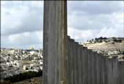 The golden shrine of the Dome of the Rock mosque in Jerusalem's Old city can be seen behind a wall being built in the village of Abu Dis on the outskirts of Jerusalem in this Dec. 29, 2003, file photo.  Israel's separation barrier will cut off 55,000 Palestinian residents of Jerusalem from their city, Israel's Cabinet acknowledged Sunday, even as it decided to push ahead with the project over strident Palestinian objections and some U.S. misgivings.