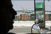 Truck driver David Zepeda, 39, is silhouetted June 28 as he drives his truck to the port of Long Beach, Calif. The twin ports of Los Angeles and Long Beach are girding themselves against the tide of goods from the Far East with a strategy to move nearly half of the landslide of cargo traffic at night and weekends.