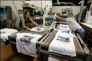Rian Busse, left, and Brenda Mulberry take Discovery launch T-shirts off the conveyor dryer Thursday at Space Shirts in Merritt Island, Fla. The area's 9,000 hotel rooms are all booked and T-shirts have been delivered to local shops.