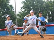 Dylan French, 11, of Barrington, throws a pitch at the University of Kansas Super Skills baseball camp while other campers watch Saturday at Hoglund Ballpark.