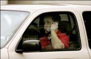 A motorist talks on a cell phone while driving in this Feb. 1 file photo, in Salt Lake City. Drivers using cellular phones are four times as likely to get into a crash that can cause injuries serious enough to send them to the hospital, said an Insurance Institute for Highway Safety study released today.