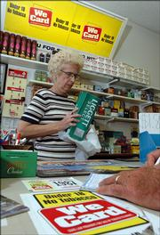 Kay Wright rings up cartons of cigarettes for a customer at Tobacco Express, 2104 W. 25th St. The store prominently displays warnings to those under 18 that they will be unable to buy tobacco there. In addition, Wright says that she asks for identification from anyone who looks under 30 years old.