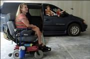 Vania Bruner, left, and her two sons, Luke, 6, center, and Logan, 4, right, hang out in the garage of their home that is under construction by Tenants to Homeowners. The east Lawrence home had to be built with special provisions including wheelchair accessible walkways and shower. Bruner and her two sons suffer from Charcot-Marie-Tooth, a hereditary form of Muscular Dystrophy.