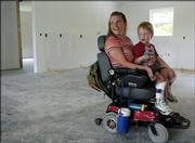 Vania Bruner, and her son Logan, 4, both from Rantoul, give a tour of their home under construction by Tenants to Homeowners. The East Lawrence home is being built with special provisions including wheelchair-accessible walkways and shower. Bruner and her two sons suffer from Charcot-Marie-Tooth disease, a hereditary neurological disorder.
