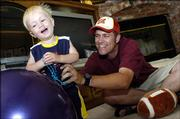 Carson Toews, left, and his father, Matt Toews, play in the living room of their south Lawrence home. Fifteen-month-old Carson is recovering from Stage 4S neuroblastoma. A benefit concert to help families like the Toews will be Saturday.