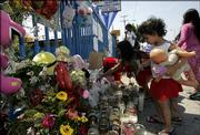 Sophie Martinez, 2, right, and Leslie Cortez, 7, place flowers at a memorial for 19-month-old Suzie Marie Pena on Friday in the Watts section of Los Angeles. It's been 40 years since a deadly riot in Watts came to symbolize America's urban despair. But tensions flared anew this week after police fatally shot the 19-month-old and her father, who clutched the girl as he fired on police responding to a 911 call.