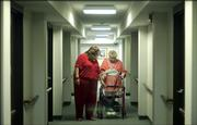 Wilma Jeffrey, 76, a resident of Babcock Place, 1700 Mass., makes her way down the hallway of her apartment building Friday, with help from her granddaughter, Amy Johnson, of Lawrence. Johnson provides regular care for her grandmother through Independence Inc.