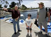 Author Richard Louv tells Tim Schultz, right, and his 6-year-old son, Nicholas, where to find trout and bass at the Miramar Reservoir in San Diego.
