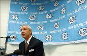 North Carolina men's basketball coach Roy Williams answers questions for reporters during the team's media day Oct. 16, 2003, at the Dean Smith Center in Chapel Hill, N.C. Williams said a communications breakdown lead to improper gifts being give to players while he was head basketball coach at Kansas University.