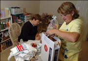 Barbara Schroeder packs a care package for a soldier deployed in Iraq as Chris Lann, left, fills out the customs form for the package. The Leavenworth duo send about 50 care packages a month to soldiers, with items ranging from snacks to toiletries to playing cards and even sports clothing.