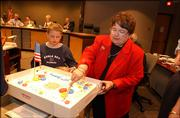 Wyatt Woods, 7, watches his grandmother, Clenece Hills, cut a cake celebrating the city of Lawrence's birthday in this Aug. 12, 2001, file photo. Hills is hoping city commissioners can find an extra $4,000 per year to host an annual birthday fest.