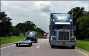 The Iowa State University solar car, left, drives at highway speed on U.S. Highway 82, Monday in Whitesboro, Okla., during the second day of the North American Solar Challenge. The Austin-to-Calgary race is the longest solar car race in the world.