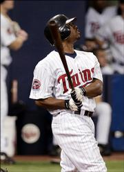 Minnesota's Jacque Jones watches his ninth-inning home run against Baltimore's Jason Grimsley. The blast gave the Twins a 3-2 victory Wednesday in Minneapolils.