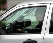 Karl Rove, President Bush's deputy chief of staff and political adviser, is seen driving away on West Executive Drive near the White House on Tuesday in Washington. Rove is at the center of a controversy about the leaking of a CIA operative's identity, which originally appeared in Robert Novak's newspaper column.