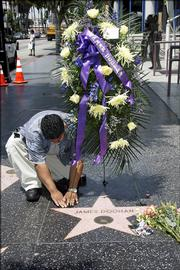 "Jimmy Hernandez places flowers on the star of actor James Doohan, best known as the burly chief engineer Montgomery ""Scotty"" Scott of the Starship Enterprise in the original ""Star Trek"" TV series. Doohan died Wednesday at his home in Redmond, Wash. The cause of death was pneumonia and Alzheimer&squot;s disease."