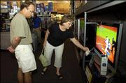 Lawrence residents Kerry and Becky Schneider browse through big-screen televisions Friday afternoon at Best Buy, 2020 W. 31st Street. With advances in high-definition television, many consumers are turning their backs on smaller TVs and setting their sights on larger models, despite the higher electricity bills.