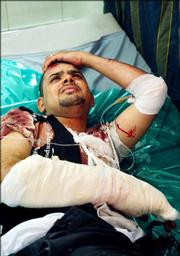 Distraught Iraqi soldier Capt. Wissam Abdul-Wahab, 24, lies in a hospital bed wounded after his wedding party was attacked by unknown gunmen killing his wife, Sally Salam, 23, and wounding two others Thursday in Baghdad, Iraq. At the time the image was made, Wahad did not know the fate of his wife.