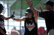 Phenix's Kalli McClure receives congratulations from a teammate and coach after scoring a run in the team's 12-2 rout of the Augusta Chill. The Phenix won Friday at the Youth Sports Inc. fields.