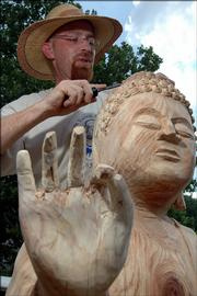 Dave Werdin-Kennicott works on carving a Buddha out of a dead locust tree at 1633 University Drive for Dr. Dave and Gunda Hiebert. Werdin-Kennicott has been working since early June on the sculpture, a replica of the Standing Amida Buddha (lower left) housed at the Spencer Museum of Art.