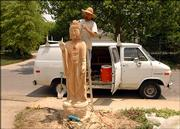 Dave Werdin-Kennicott has spent weeks creating a Buddha statue at 1633 University Drive. The locust tree was dying when it was cut down, leaving a tall stump for the artist to sculpt the figure.