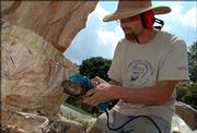 Dave Werdin-Kennicott removes wood from the lotus-flower base of a Buddha sculpture he's carving from a dead locust tree stump. Werdin-Kennicott has used chisels, sanders, grinders, drills and even chain saws on the project.