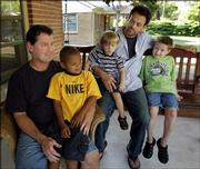 Bill Dunn, left, holds Haden, 5, while Shaun Morse holds Henry, 2 , and Nathan, 6, on the front porch of their home in Wichita. Both Dunn and Morse are listed as parents of the California adopted boys. Kansas state law is silent on whether gays or lesbians can adopt foster children.