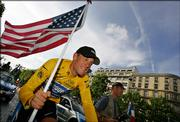 Lance Armstrong flies the colors during a victory parade on the Champs-Elysees after winning his seventh straight Tour de France. Armstrong claimed his unprecedented victory Sunday in Paris.