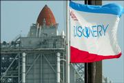 Space shuttle Discovery's flag waves in the breeze Sunday as Discovery sits on the pad covered by the rotating service structure at Kennedy Space Center in Cape Canaveral, Fla. The countdown is under way for a Tuesday morning launch.