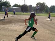 Mad Batters base runner Erica Lignell runs to first base during a Lawrence Girls Fast Pitch Assn. game against the Falcons on Thursday at Holcom. The Falcons won the game 15-5.