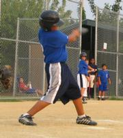 Cubs player Carlos Florez swings at a pitch during a Jhawk Baseball game at Holcom.