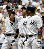 New York's Gary Sheffield celebrates with teammates Derek Jeter, left, and Robinson Cano, right, after Sheffield hit a three-run home run. The Yankees beat the Twins, 6-3, Thursday in New York.