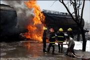Iraqi firefighters douse flames from an exploded fuel tanker train carriage in the Dora area of Baghdad, Iraq.   A train carrying fuel exploded into flames Thursday when a trackside bomb struck a fuel tank carriage, killing two people, police said.