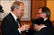 U.S. diplomat Christopher Hill, left, chats with Russia's Alexander Alexeyev, right, and Japan's Kenichiro Sasae.