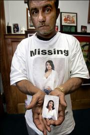 Melvin Figueroa holds a photo of his 24-year-old daughter, LaToyia Figueroa, Thursday in Philadelphia. Latoyia, who is five months pregnant and has a 7-year-old daughter, was last seen walking from a friend's home July 18 after going to a doctor's appointment.