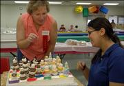Ten pounds of sugar, some food coloring and a whole lot of time helped Lone Star 4-H Club member Christine Caffey, 15, Lawrence, create a unique chess cake. Karen Blakeslee, Manhattan, a food preparation judge, consults with Caffey on her cake Monday during judging. Caffey won a purple ribbon in the Cooking for Fun category in the 15-19 year-old division.