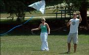 Alyssa Rulewicz, KU senior from Edmond, Okla., and Rob Gandy, Emporia State University senior from Olathe, search for a breeze to send their kite soaring in Watson Park on Monday. The city is keeping Watson Park pesticide-free in a test project.