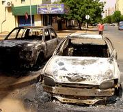 People look over the remains of cars destroyed by protesters who took to the streets in Khartoum, Sudan, after the announcement of the death of former rebel leader and First Vice President John Garang in a helicopter crash. Garang supporters tore through the capital in riots that left at least 49 people dead, smashing cars and shops and angrily blaming the government for their hero's death.