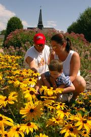 Jeff and Heather Wedgewood and their son, Gabriel, take time out of their bike ride to stop and smell the flowers at the Visitor Center in North Lawrence, which sports one of the city's best-looking gardens.