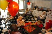 Brandon Woods activities coordinator Hannah Hamlin plays a game of checkers with residents Hettie Butler, left, Darlene Saile and other residents Thursday in the retirement community's new Coca-Cola parlor.