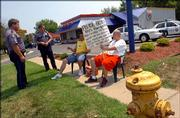 Lawrence Police Sgt. Dave Hubbel, left, and Officer Eric Maack talk to protesters Aaron Brackett, of Mid-Central Tile, of Grain Valley, Mo., and friend Harold Eads, Independence, Mo., Wednesday at Burger King, 1107 W. Sixth St.